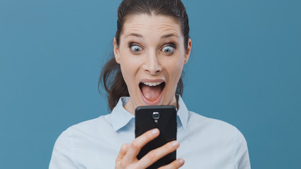 Shocked woman using a smartphone and connecting