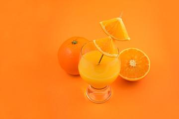 Orange juice stock images. Glass of orange juice with oranges. Orange on orange background. Juicy pieces of oranges