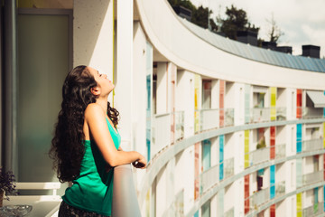 Young woman relaxing at the sun in the balcony
