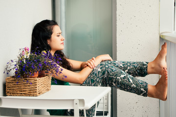Young woman relaxing sitting in her balcony