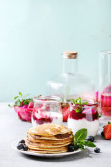 Stack of homemade pancakes served on plate with berries, mint, glass jars of yogurt, bottle of lemonade, fruit salad in pink dragon fruit over grey texture table.