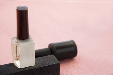 Bottle of gel nail polish on pink background with copy space, closeup.