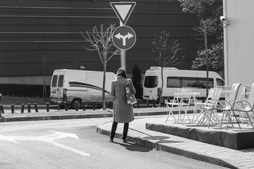 woman standing in front of a road sign and wondering where to go. choosing where to go. dilemma which way to catch.