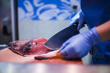 fishmonger cutting piece of red tuna