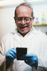 59  year  old man with smartphone and latex gloves
