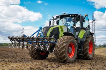 Ackerbau - Traktor mit vorgebauter Egge beim Maislegen