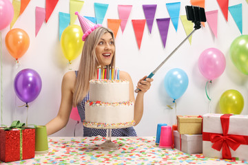 Young woman celebrating her birthday and taking a selfie
