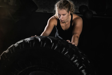 Young Woman Flipping Heavy Tire