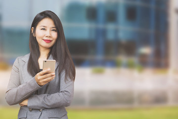 beautiful Asian business woman with smart phone in hand standing outdoor over blur building smiling at a camera