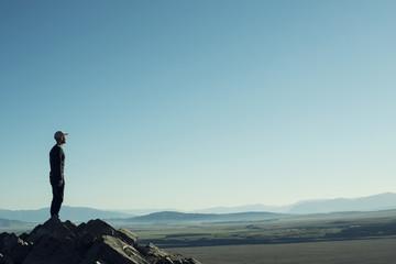 Retrato de hombre a contraluz en la cima de una montaña rocosa. Cielo azul al atardecer.