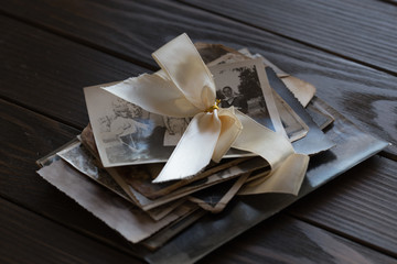 stack of Black and white family photos laid on wooden floor background.