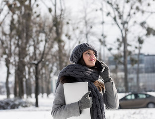 Woman with laptop in winter forest