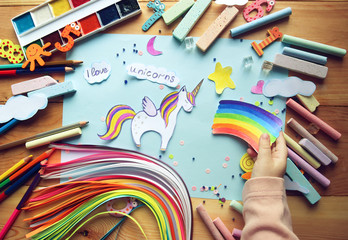 the child makes an applique with a unicorn and a rainbow