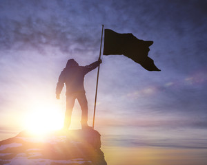 silhouette of man with flag of victory on top of a mountain over sky and sun light background. business, success, leadership, achievement and the concept of people.