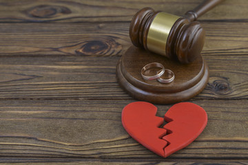 figure of a broken red heart, two wedding rings, gavel, hammer of a judge on a wooden background. Divorce proceedings, the dissolution of marriage. court, law.