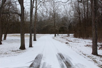 The snow covered park road on a cold winter day.