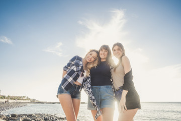 Three young beauty women at the beach join the summer