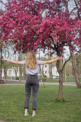 Young woman enthusiastic, embraces the wildly blossoming apple tree in the public park