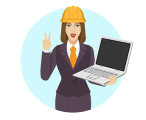 Businesswoman in construction helmet holding a laptop notebook and showing victory sign