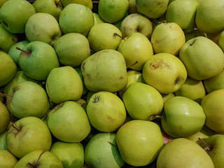 Fresh green apples lie in the shop window