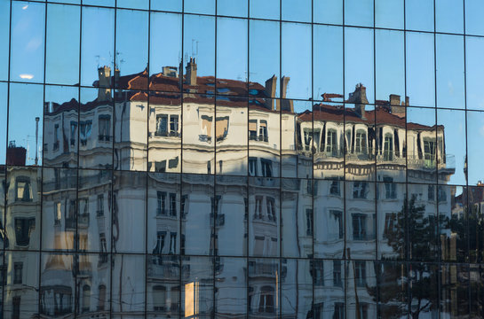 Old buildings reflected in the windows of modern architecture in Lyon, France.
