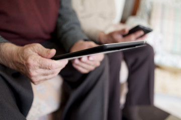old woman and old man using electronic devices