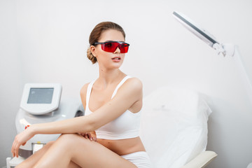 Portrait of attractive young fresh healthy woman in white lingerie, natural make-up and red safety goggles sitting on the beauty salon chair and looking aside.