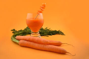 Carrot juice stock images. Glass of carrot juice with oranges. Carrot on orange background
