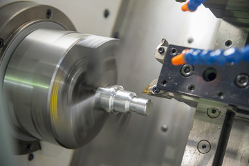 The  CNC lathe machine cutting thread at the metal shaft part