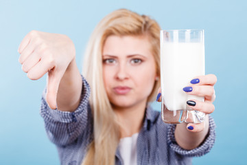 Woman holding milk glass showing thumb down