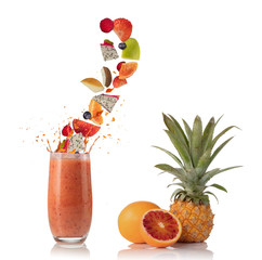 Smoothie drink with fruit flying ingredients on white