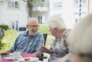 Senior people talking on breakfast table