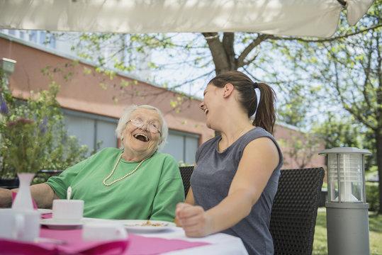 Senior woman laughing with nurse at nursing home