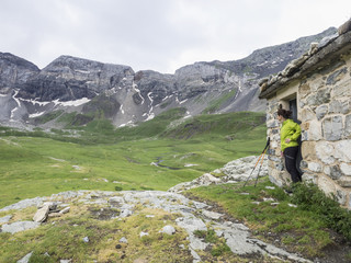 Woman hiker admiring scenic view of Cirque de Troumouse from mountain hut, France