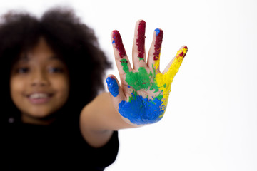 African American playful and creative kid getting hands dirty with many colors - in white isolated background.