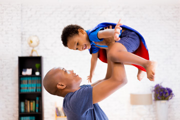 Father lifting son up with super hero costume at home