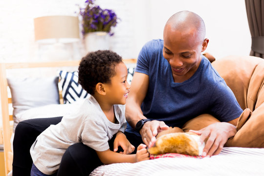 African American family of two playing with a dog pet in bedroom