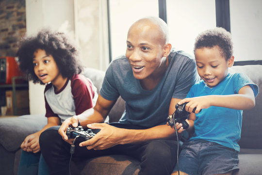 African American family at home sitting in sofa couch and playing console video games together.