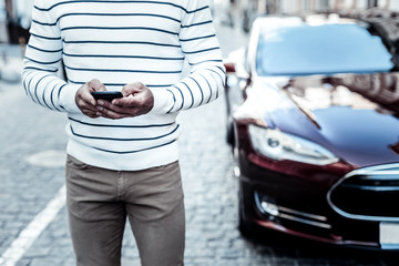 Modern device. Close up of a smartphone being in use by a pleasant nice man while standing near his car