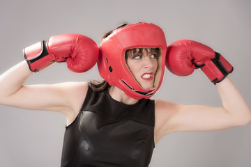 Woman boxer with an facial expression wearing a red headguard and red boxing gloves, Circa 2018