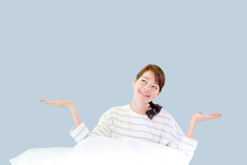 Beautiful young smiling asian woman sitting on bed and Raise arm in the morning at bedroom. isoleted blue background image.
