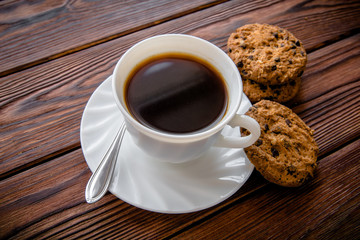 A cup of hot coffee stands on a wooden table