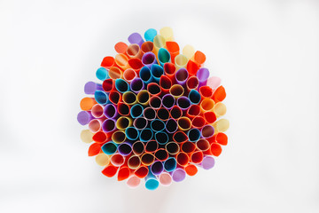 pile of colorful cocktail straws over white background