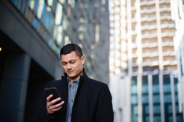 Young adult male checking smartphone in city