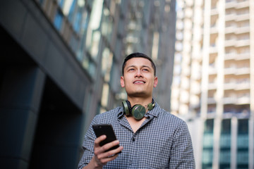 Young adult male with smartphone in city