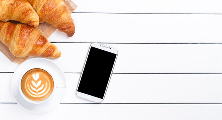 phone croissant coffee view from above wooden white background