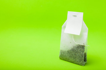 A new tea bag on a green background. Copy space, mockup.