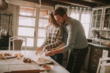 Loving couple preparing pasta in the kitchen