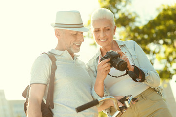 High resolution photos. Positive nice elderly woman holding a photo camera and showing photos to her husband while having a walk with him