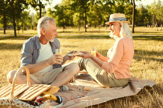 In the park. Positive nice delighted couple looking at each other and passing food while enjoying their picnic